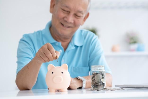 Uomo anziano che sorride mettendo una moneta all'interno del salvadanaio come risparmio per investimenti e piallatura di risparmio previdenziale.