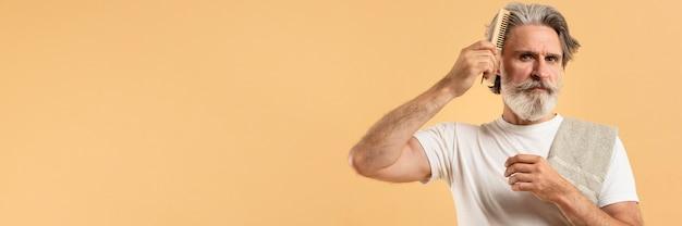 Uomo anziano con un asciugamano che si pettina i capelli