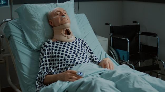 Paziente anziano seduto nel letto del reparto ospedaliero con collare cervicale