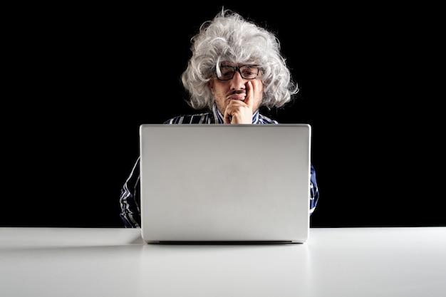 Un uomo anziano serio perso nei pensieri davanti a un computer portatile, boomer concentrato o pensiero distratto della soluzione del problema, domanda ponderata senior preoccupata perplessa al lavoro