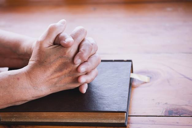 La donna più anziana prega con una sacra bibbia