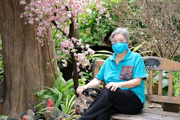 Donna anziana che indossa una maschera facciale che riposa in giardino. femmina anziana asiatica rilassante all'aperto. stile di vita per il tempo libero senior