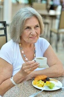 Donna anziana con colazione e caffè fuori