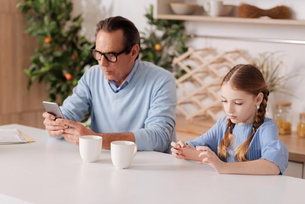 Pensionato interessato di età compresa tra gli anziani che si siede in casa e utilizza lo smartphone con la nipote mentre naviga in internet e controlla i profili dei social media