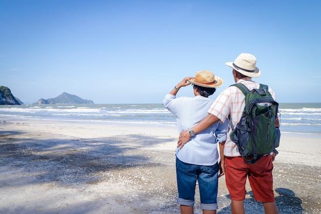 Una coppia asiatica anziana che si abbracciano sulla spiaggia