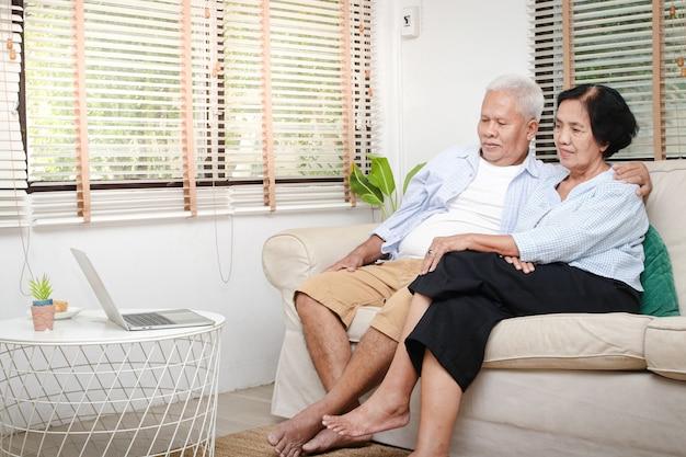 Anziana coppia asiatica guarda i media online sul proprio laptop nel soggiorno di casa. concetto di vita dopo il pensionamento