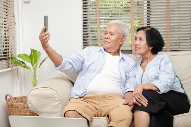 Anziana coppia asiatica guarda i media online sul proprio smartphone nel soggiorno di casa. concetto di vita dopo il pensionamento