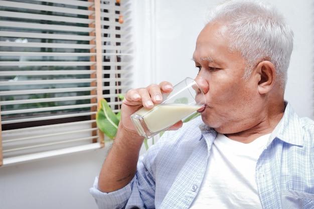 L'uomo asiatico anziano beve latte contenente calcio per prevenire l'osteoporosi. rendi il corpo forte e sano. concetto di cibo e nutrizione per gli anziani