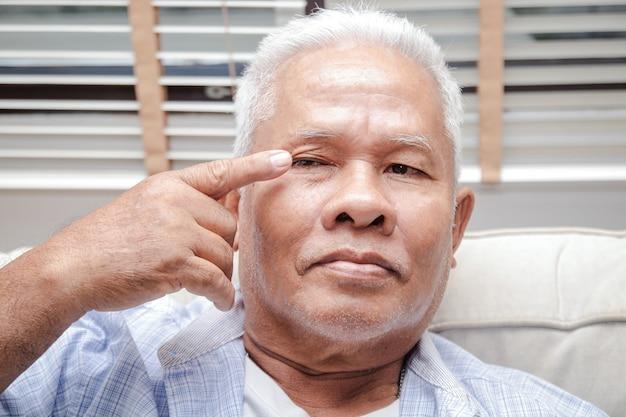Un uomo asiatico anziano ha irritazione agli occhi