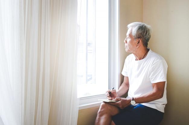 Un anziano uomo asiatico si siede vicino alla finestra