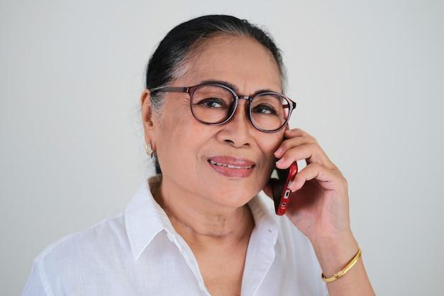 Donna asiatica anziana che sorride mentre risponde a una telefonata