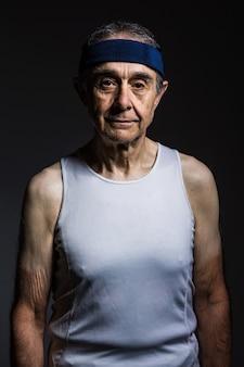 Atleta anziano che indossa una maglietta bianca senza maniche, con segni di sole sulle braccia e fascia blu, su uno sfondo scuro. sport e concetto di vittoria.