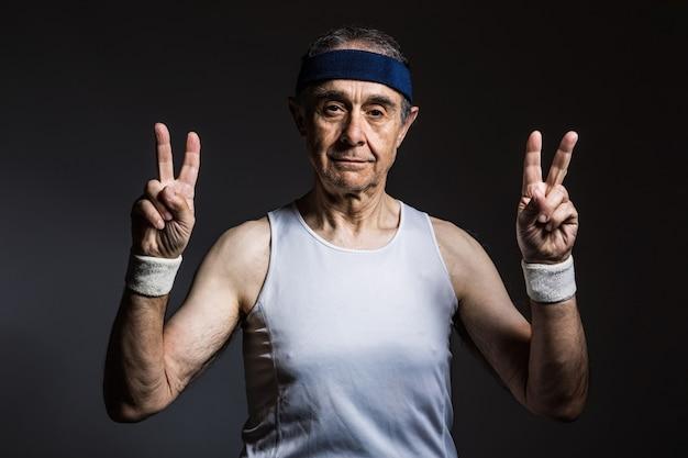 Atleta anziano che indossa una maglietta bianca senza maniche, con segni di sole sulle braccia e fascia blu, che fa il segno della vittoria con le dita, su uno sfondo scuro. sport e concetto di vittoria.