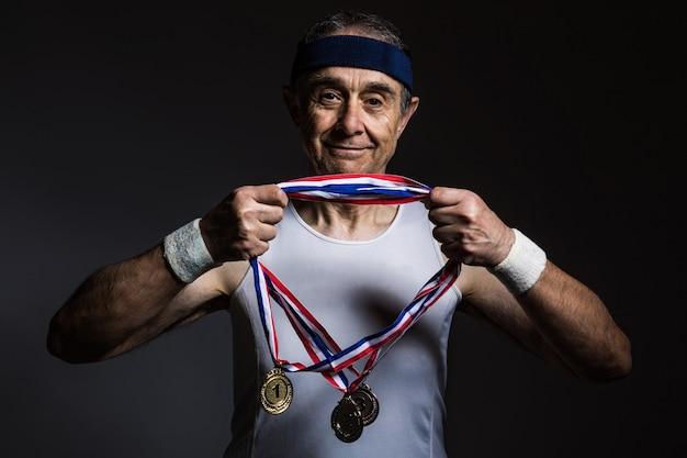 Atleta anziano che indossa una camicia bianca senza maniche, con segni di sole sulle braccia, che si mette tre medaglie sul collo, su uno sfondo scuro. sport e concetto di vittoria.