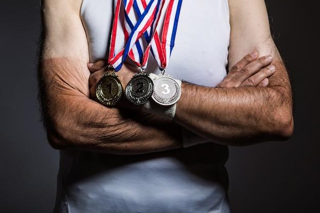 Atleta anziano che indossa una maglietta bianca senza maniche, con segni del sole sulle braccia, con tre medaglie sul collo, con le braccia incrociate, su uno sfondo scuro. sport e concetto di vittoria.