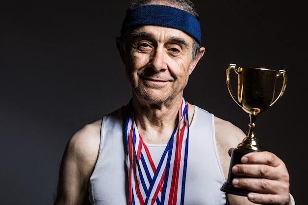 Atleta anziano che indossa una maglietta bianca senza maniche, con segni del sole sulle braccia, con tre medaglie sul collo, con un trofeo tra le mani, su uno sfondo scuro. sport e concetto di vittoria.