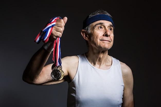 Atleta anziano che indossa una camicia bianca senza maniche, con segni di sole sulle braccia, con tre medaglie in una delle sue mani, su uno sfondo scuro. sport e concetto di vittoria.