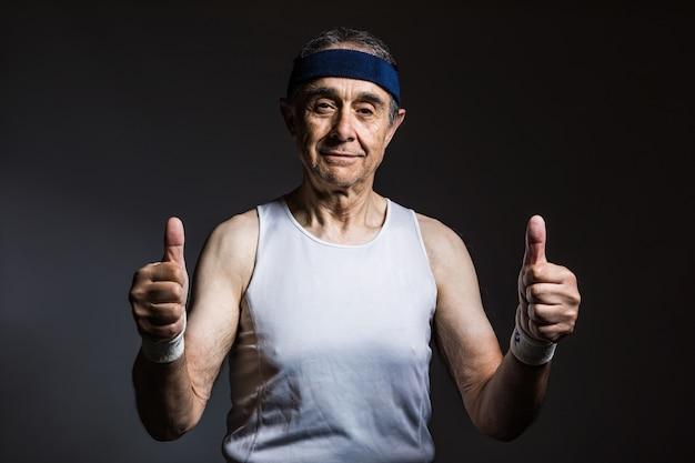Atleta anziano che indossa canotta bianca, con segni di sole sulle braccia e fascia blu, pollice in alto, su uno sfondo scuro. sport e concetto di vittoria.