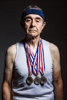 Atleta anziano che indossa una canotta bianca, con segni di sole sulle braccia, con tre medaglie sul collo, che le mostrano, su uno sfondo scuro. sport e concetto di vittoria