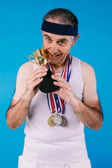 Atleta anziano con segni di sole sulle braccia, con tre medaglie sul collo che morde un trofeo, su sfondo blu
