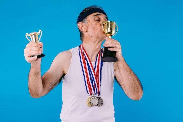 Atleta anziano con segni di sole sulle braccia, con tre medaglie sul collo che bacia un trofeo, su sfondo blu