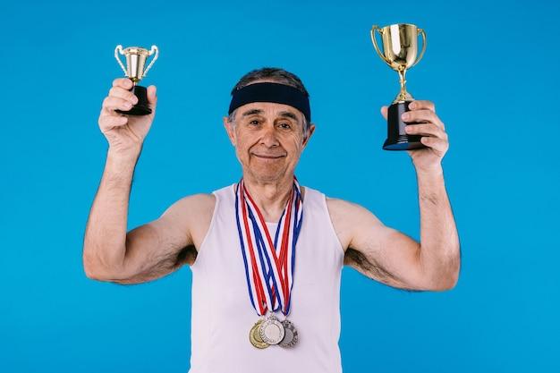 Atleta anziano con segni di sole sulle braccia, con tre medaglie al collo e due trofei in mano, su sfondo blu