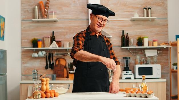 Tavolo infarinato per anziano fornaio per infornare e fare deliziosi biscotti. chef senior in pensione con bonete e grembiule in uniforme spolverata setacciatura setacciatura ingredienti grezzi a mano che cuoce pizza fatta in casa, pane