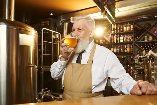 Anziano barman barbuto in grembiule marrone in piedi al bancone del bar in mini birreria e bere birra fredda e gustosa. bel birrificio esperto di degustazione di birra, guardando lontano.