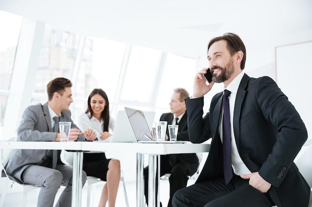 Uomo d'affari anziano seduto al tavolo con i partner commerciali e parlando al telefono
