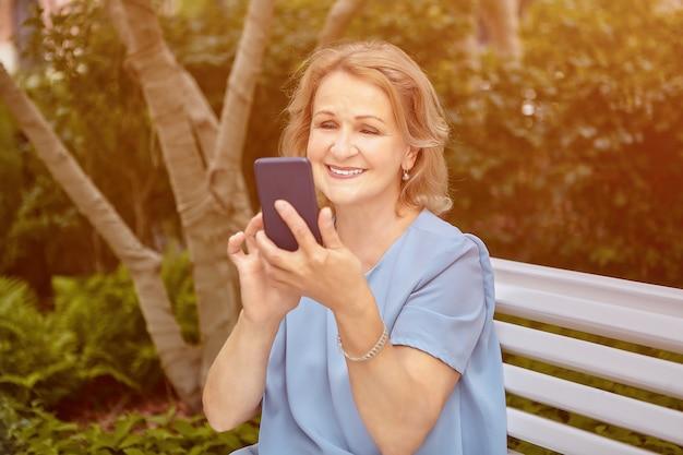 La signora attraente caucasica anziana di circa 62 anni sta usando il suo telefono delle cellule mentre si siede sulla panchina nel parco pubblico.