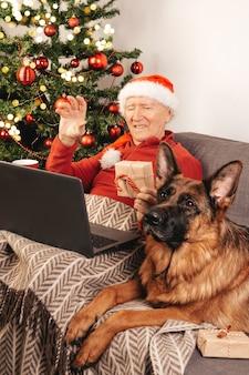 Uomo caucasico anziano in cappello della santa con il computer portatile che si siede su un divano vicino a un albero di natale con scatola regalo e cane pastore tedesco in chat con i parenti online. autoisolamento, atmosfera vacanziera.