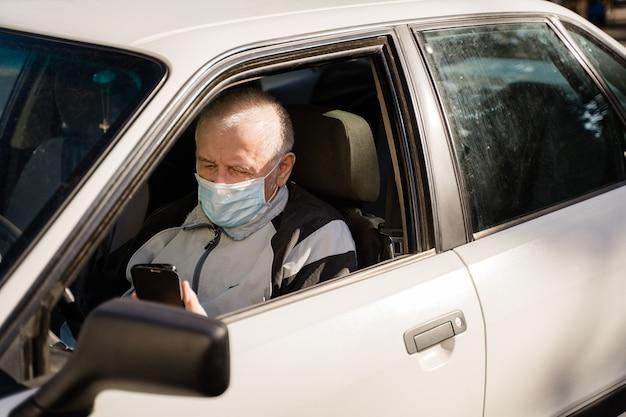 Anziano uomo caucasico seduto in macchina e utilizzando il telefono. pensionati moderni attivi. filmati 4k di alta qualità
