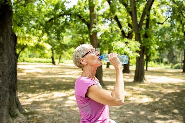 Donna caucasica anziana che si prende una pausa e beve acqua dopo un lungo allenamento in natura.