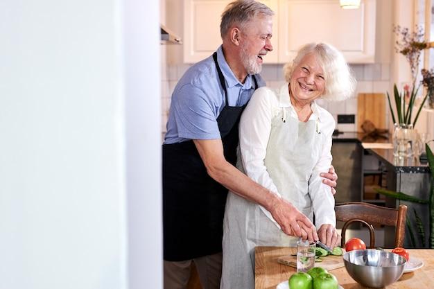 Coppia di anziani intagliare verdure insieme, uomo dai capelli handsomegray aiutare la moglie a cucinare