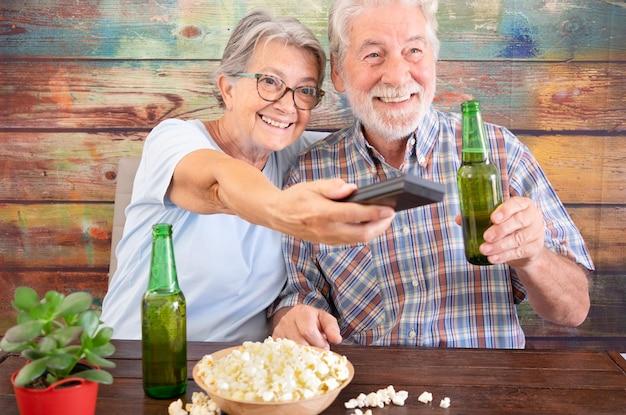 Coppia di anziani divertirsi guardando una partita di calcio in tv. bottiglie di birra e popcorn in tavola