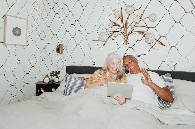 Coppia di anziani che fa una videochiamata a letto