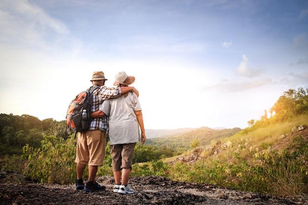Coppia di anziani, escursioni e in piedi su un'alta montagna, sono felici in pensione.