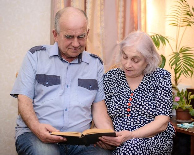 Una coppia di anziani che tiene un libro e lo legge insieme a casa