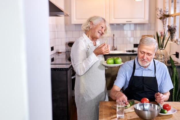 Coppia di anziani in cucina a casa, uomo anziano in grembiule siede intagliare verdure fresche, donna dai capelli grigi che tiene le mele nelle mani e parla con lui