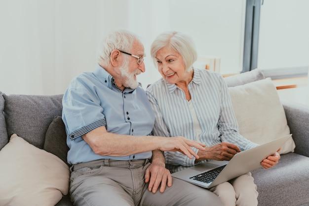 Coppia anziana che fa shopping online su internet con un computer portatile a casa - bella gente anziana felice che utilizza app per pc e social network