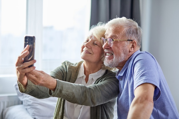 Coppia di anziani che cattura foto su smartphone, seduti in camera da letto, siedono sorridendo. concetto di tecnologia dello stile di vita della società di persone anziane. uomo e donna condividono i social media insieme nella casa del benessere