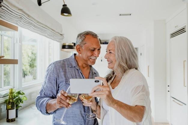 Coppia di anziani che si fanno un selfie mentre bevono un vino