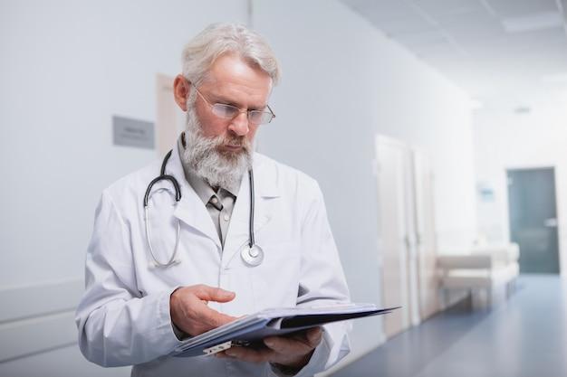 Medico anziano che controlla le carte nel corridoio della clinica