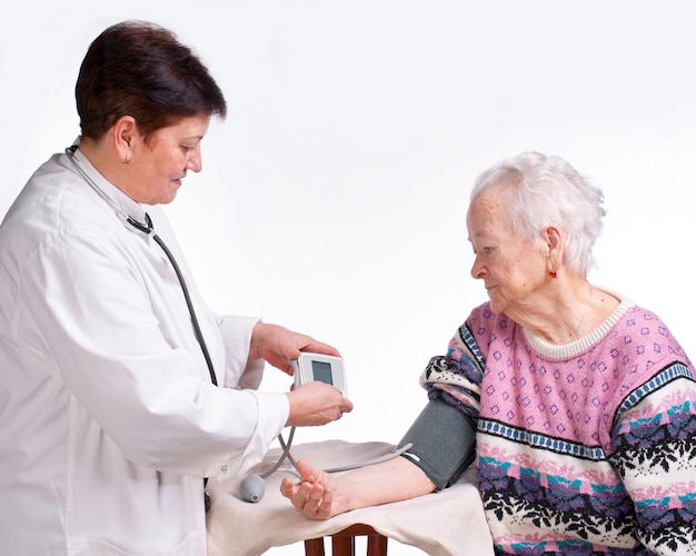 Medico e paziente anziani. misurazione della pressione