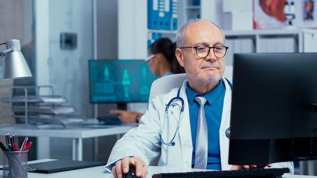 Medico anziano che lavora al pc in una moderna clinica privata con pareti di vetro. professionisti ospedalieri nel settore sanitario personale al lavoro in medicina medico specialista in unifor al lavoro d'ufficio