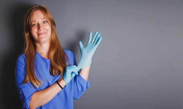 La donna anziana in camice blu mette sulle mani guanti sterili protettivi su sfondo grigio