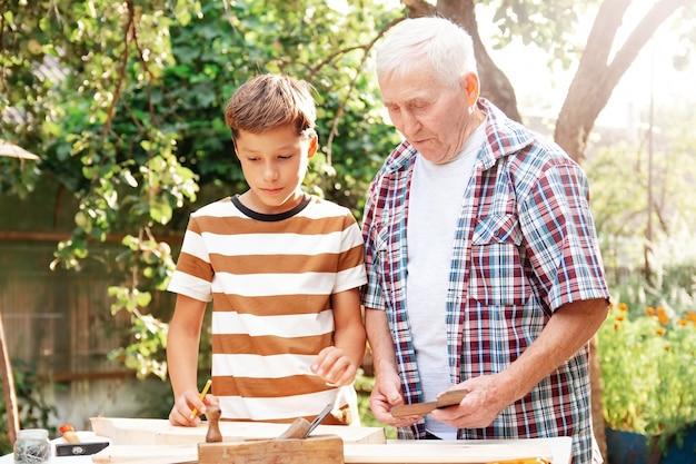 Anziano uomo anziano dai capelli grigi e ragazzo adolescente sono in piedi al tavolo con gli strumenti. il nonno insegna a suo nipote la falegnameria.