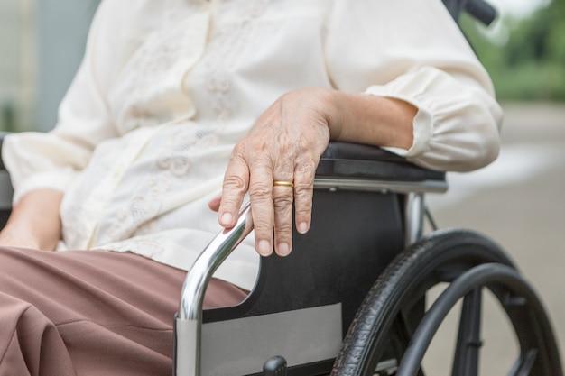 Mani anziane su una sedia a rotelle.