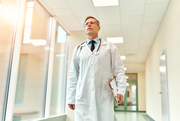 Un anziano medico serio bello in bicchieri con uno stetoscopio cammina lungo il corridoio della clinica con in mano una tessera paziente.