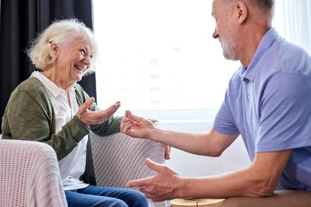 Il marito anziano ha fatto una sorpresa per sua moglie, per favore, un uomo dai capelli grigi presenta un regalo a una donna anziana piacevolmente sorpresa, regala l'anello